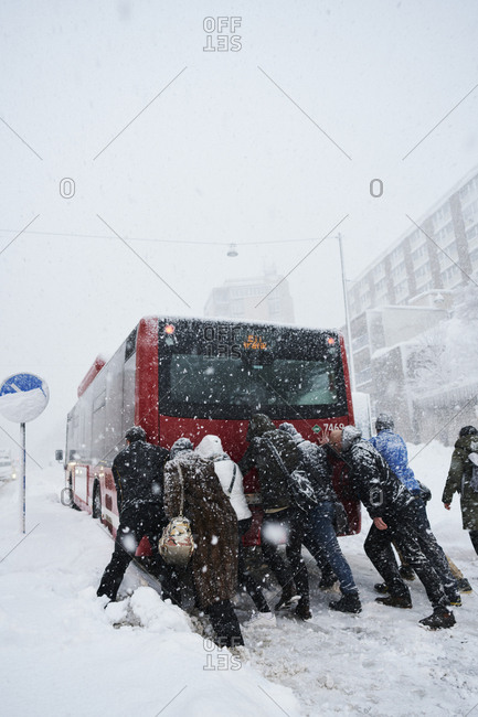Sweden, Stockholm, Sodermalm, Folkungagatan, People pushing bus in winter