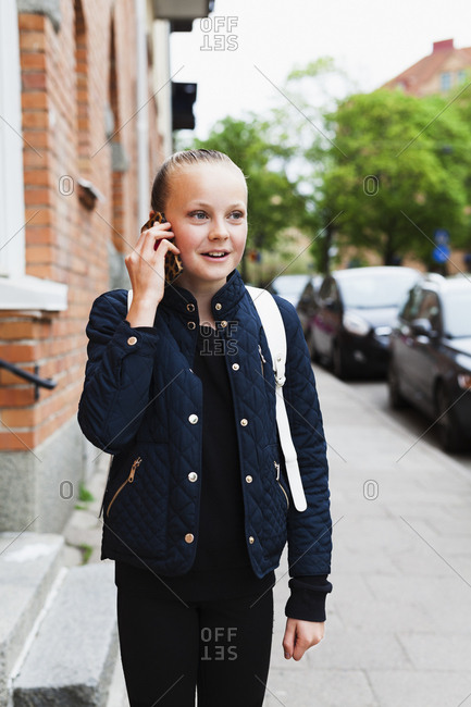 Sweden, Uppland, Solna, Girl smiling while talking on phone
