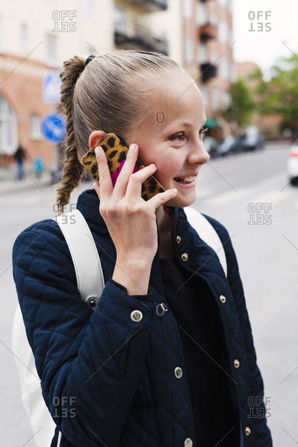Sweden, Uppland, Solna, Girl smiling while talking on phone