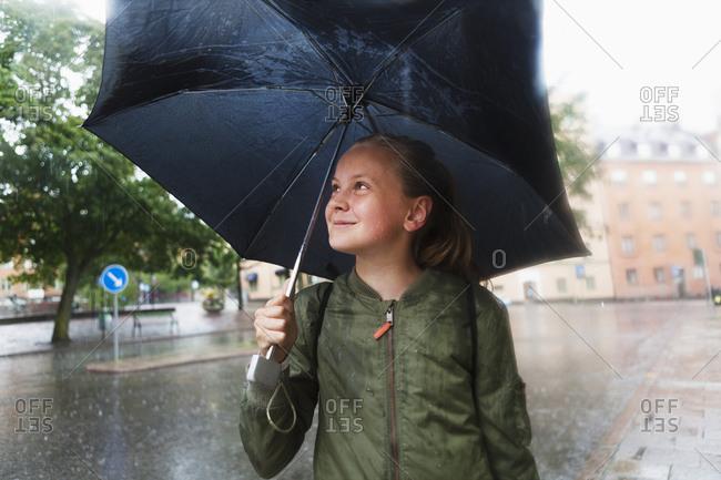 Sweden, Uppland, Solna, Resunda torg, Girl carrying umbrella and smiling