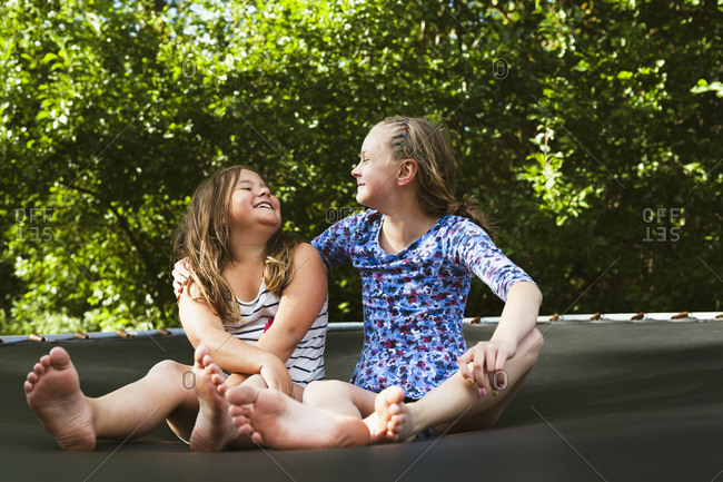 Sweden, Oland, Two girls, sitting on trampoline on sunny day