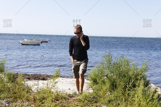 Sweden, Skane, Hollviken, Man talking on phone by sea