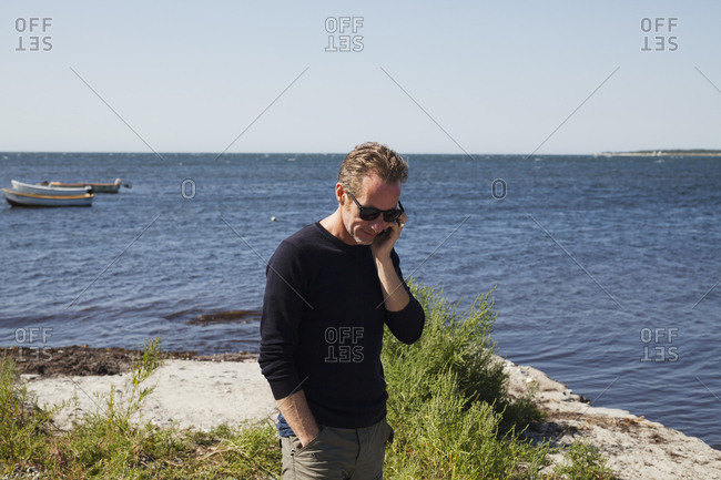 Sweden, Skane, Hollviken, Man talking on phone by sea