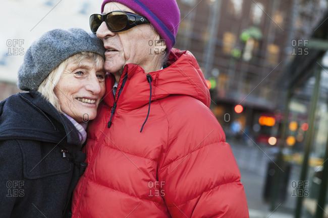 Sweden, Stockholm, Sodermalm, Senior couple hugging at bus stop