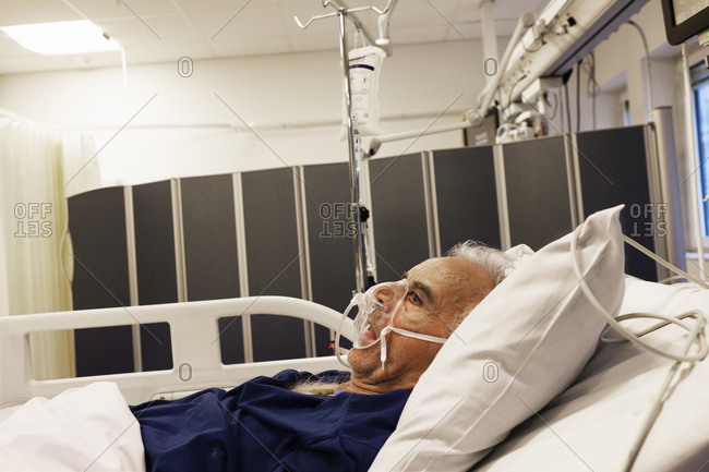 Sweden, Senior man lying down on hospital bed