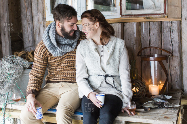 Sweden, Young couple sitting on wooden table and talking