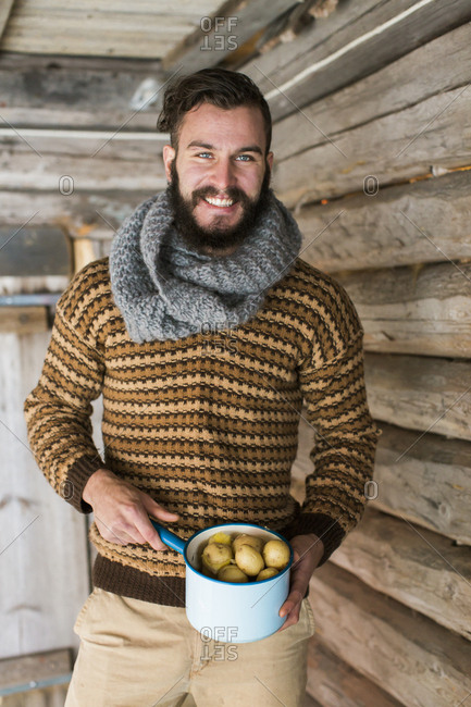 Sweden, Portrait of young man holding pot of potatoes