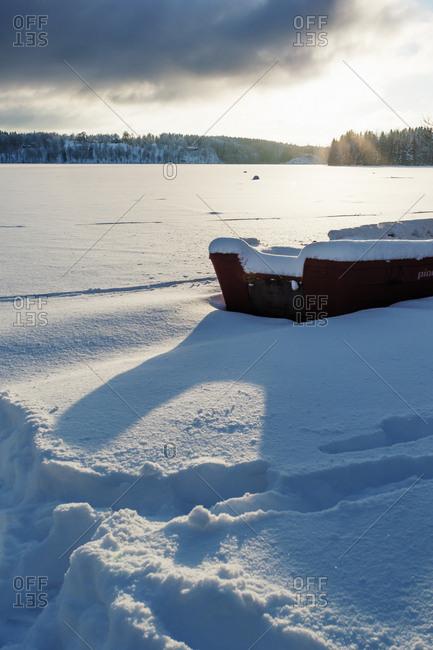 Sweden, Vastra Gotaland, Viaredssjon, Frozen lake with boat in snow