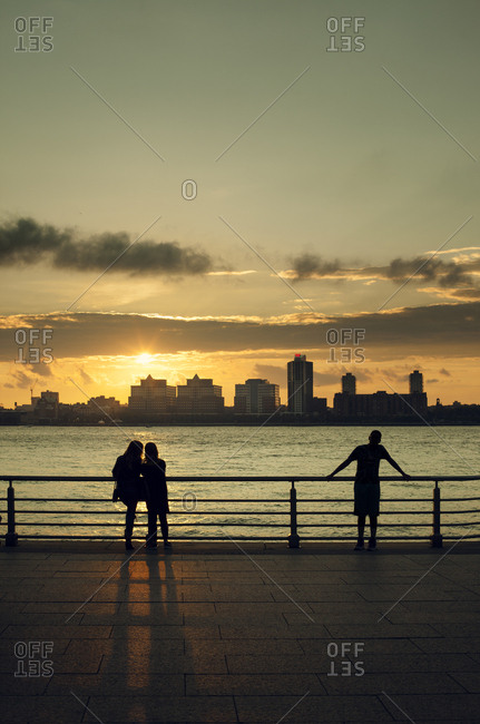 USA, New York, New York City, People looking at Manhattan skyline at sunset