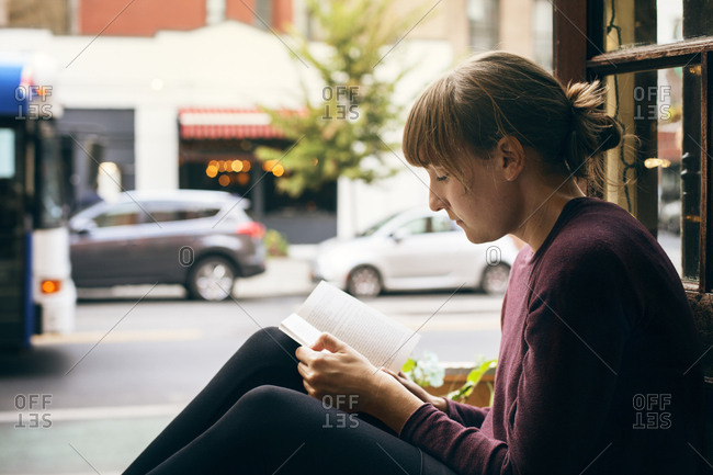 USA, New York, New York City, West Village, Mid adult woman reading