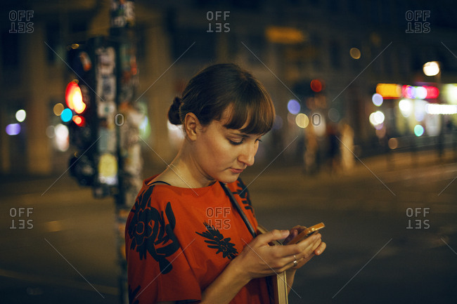 Germany, Berlin, Beautiful woman texting in city at night