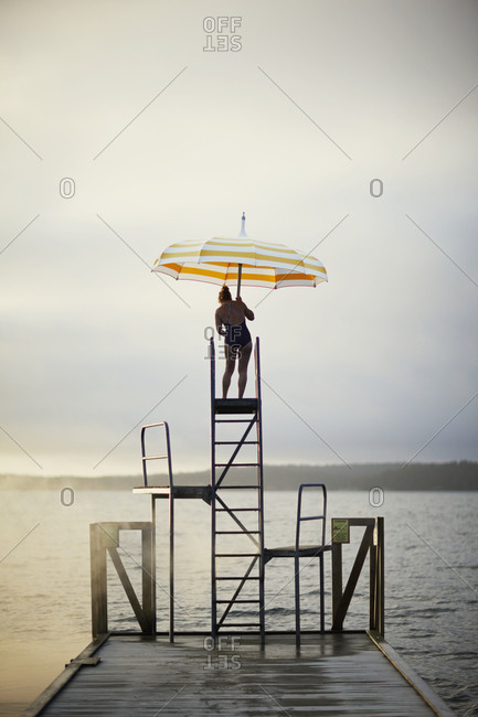 Sweden, Sodermanland, Woman with umbrella standing on ladder by lake