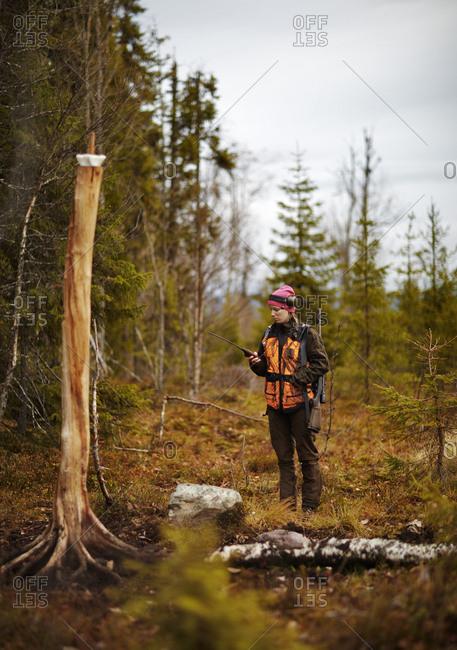 Sweden, Vasterbotten, Female hunter using satellite phone in forest