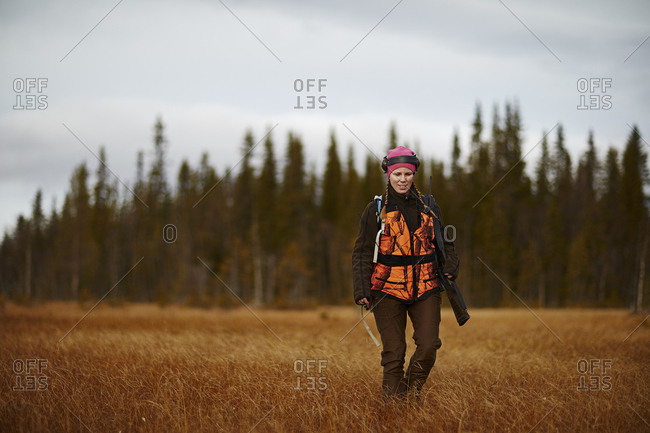 Sweden, Vasterbotten, Female hunter walking in field