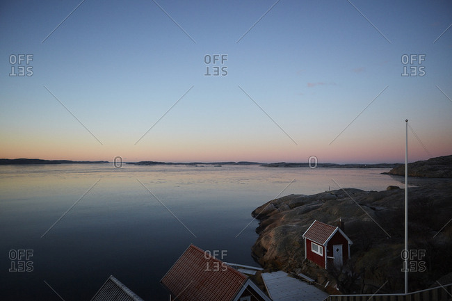 Sweden, West Coast, Lysekil, Scenic landscape with houses at sunset
