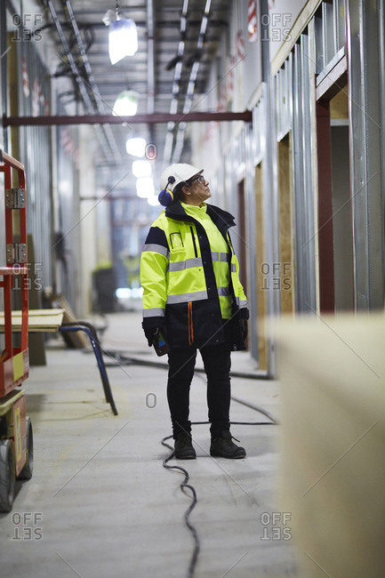 Sweden, Woman in protective clothing standing and looking away