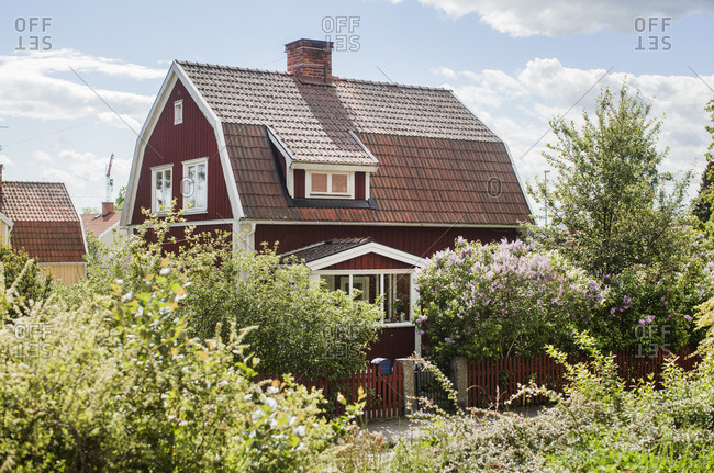 Sweden, Vastmanland, Vasteras, Wooden house in bushes on sunny day