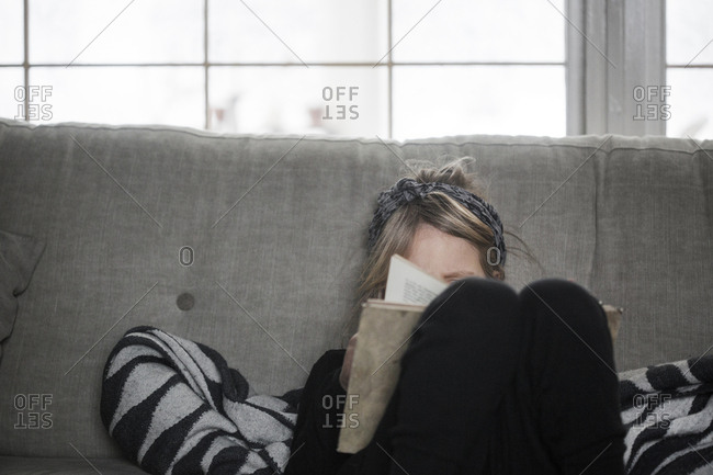 Sweden, Girl reading book on sofa