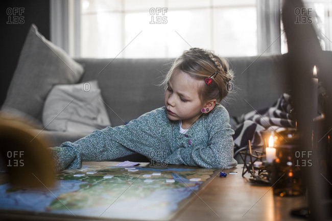 Sweden, Girl playing board game on coffee table
