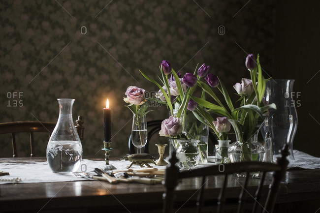 Sweden, Wooden table with candle burning, vases, and flowers in vase