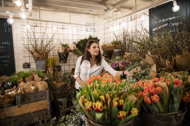 Sweden, Woman choosing flowers in shop