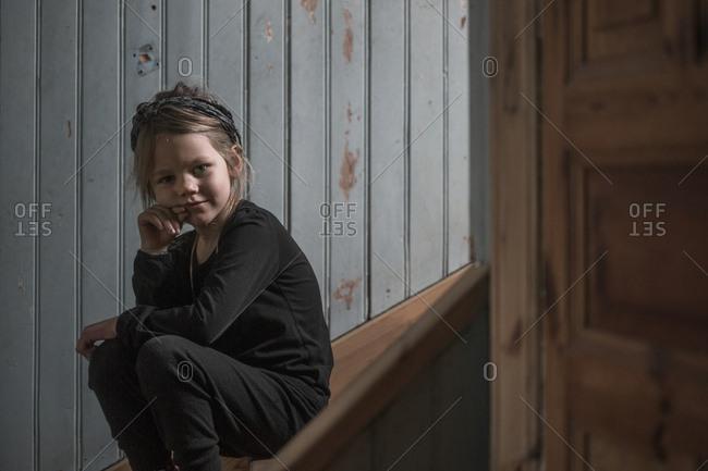 Sweden, Portrait of blonde girl sitting on wooden steps