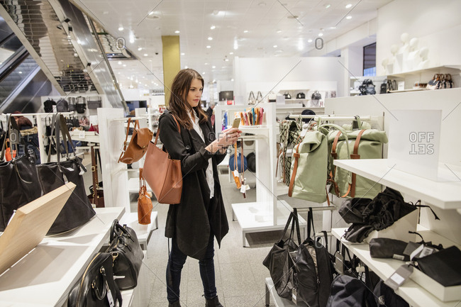 Sweden, Woman photographing clothes in shop