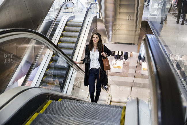 Sweden, Woman on escalator in shopping center