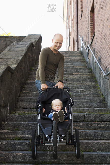 Sweden, Gotaland, Vastra, Stay at home dad pushing stroller with son