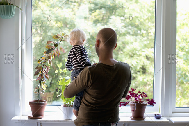 Sweden, Stay at home dad holding son while looking through window