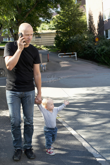 Sweden, Father and son walking in city street