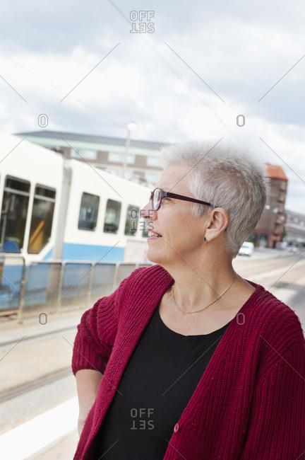 Sweden, Senior woman at tram station