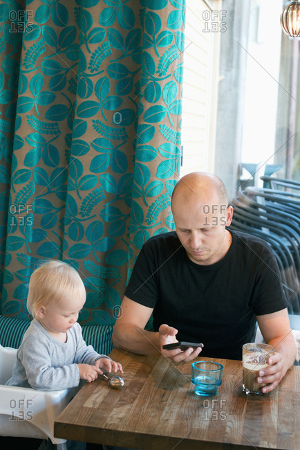 Sweden, Father and son sitting at table, father using smart phone