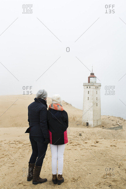 Denmark, Nordjylland, Lokken, Mother and daughter looking at Rubjerg Knude fyr lighthouse