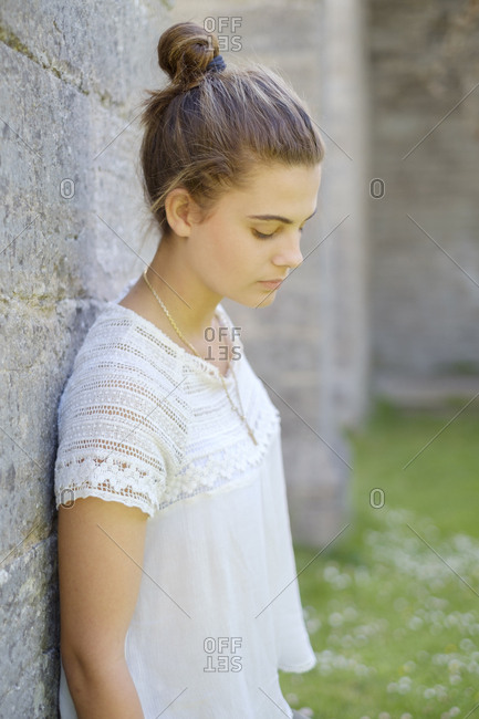 Sweden, Ostergotland, Portrait of teenage girl leaning against wall outdoors
