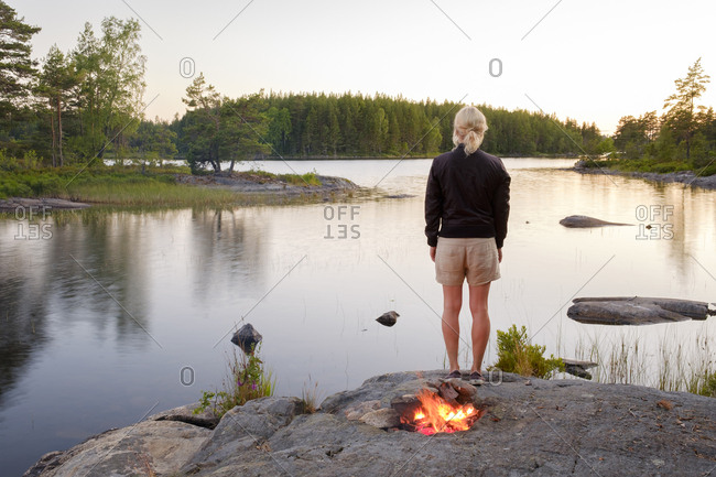 Sweden, Ostergotland, Woman standing at lake side near bonfire