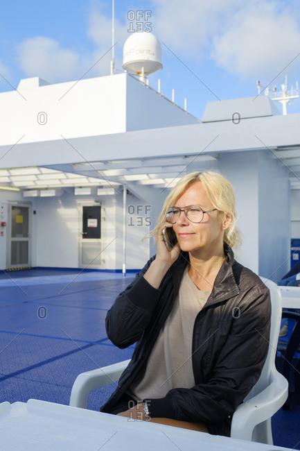 Sweden, Woman sitting on ferry deck, talking on smartphone
