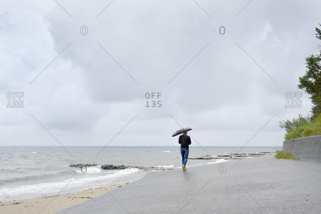 Poland, Niechorze, Woman under black umbrella walking on beach