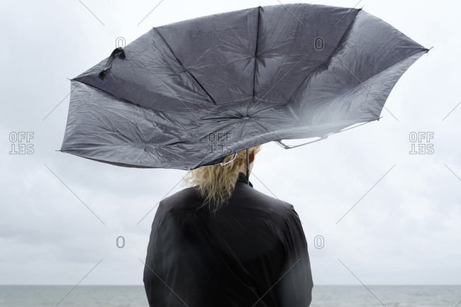 Poland, Niechorze, Woman under black umbrella watching Baltic Sea