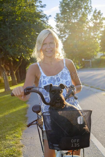 Sweden, Ostergotland, Finspang, Woman on bike with dog in bike basket