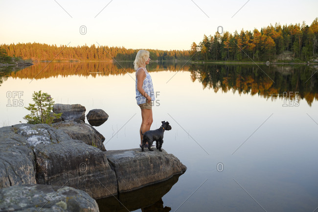 Sweden, Ostergotland, Skiren, Woman and dog looking at view at lake side