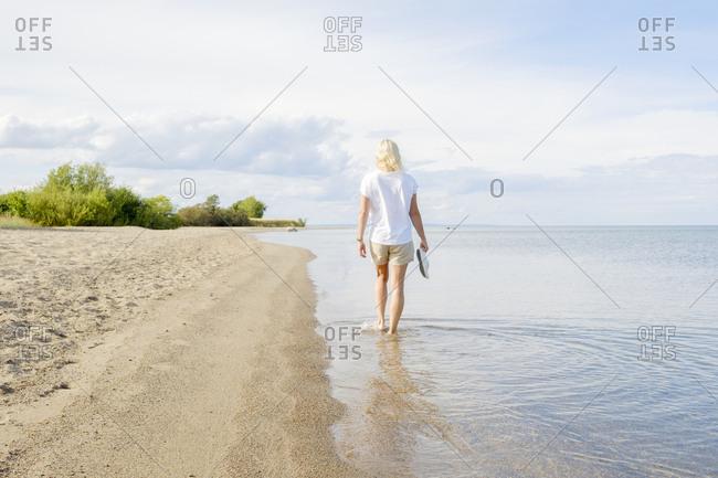 Sweden, Smaland, Visingso, Vattern, Woman walking on beach at lakeside