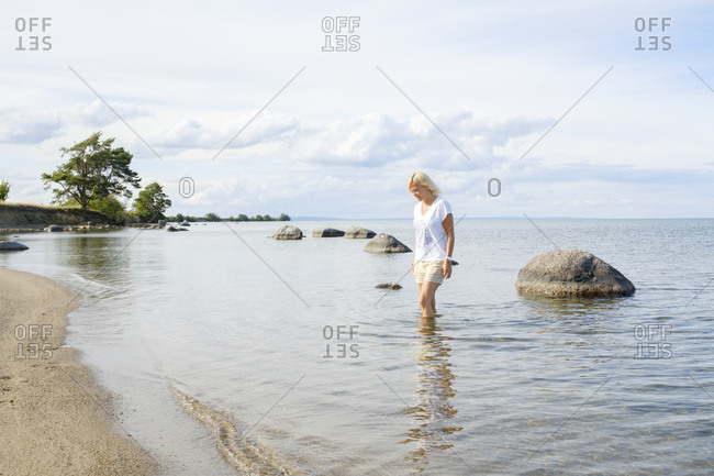 Sweden, Smaland, Visingso, Vattern, Woman wading in water on beach at lakeside