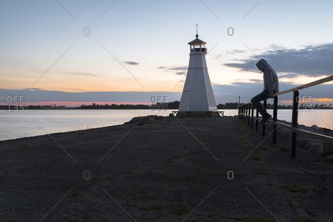 Sweden, Ostergotland, Vadstena, Vattern, Man sitting on railing by lake, lighthouse in background