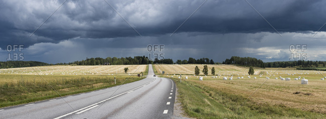 Sweden, Sodermanland, Stora Malm, Storm clouds over country road