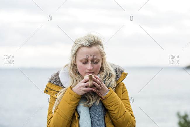 Sweden, Sodermanland, Young blonde woman drinking coffee by sea