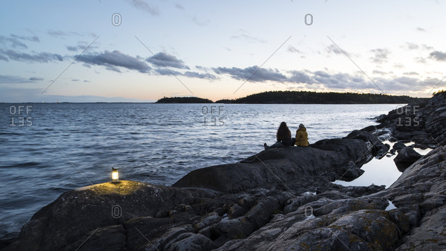 Sweden, Sodermanland, Braviken, Teenage girl sitting with young woman on seashore at dusk