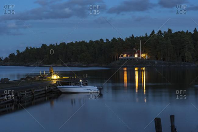 Sweden, Sodermanland, Braviken, Woman standing on jetty at dusk