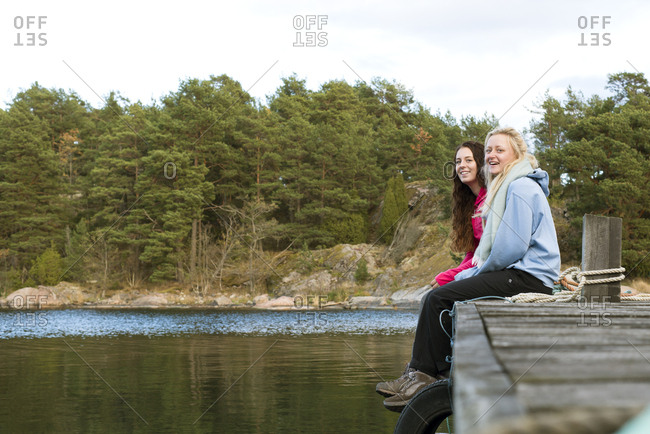 Sweden, Sodermanland, Braviken, Teenage girl sitting with young woman on jetty