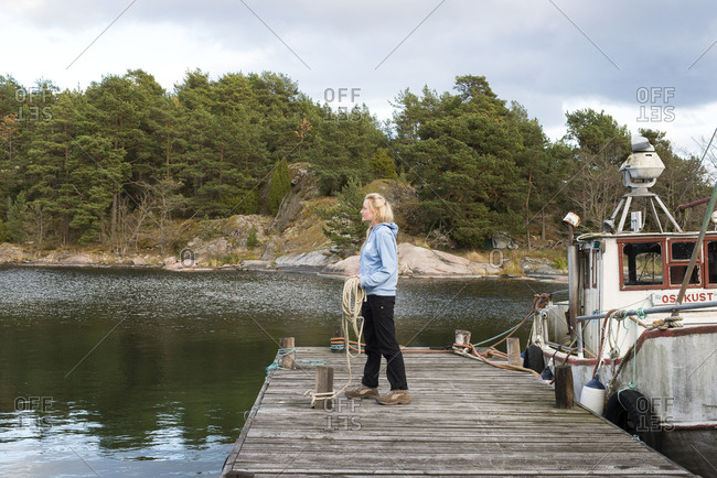 Sweden, Sodermanland, Braviken, Young woman holding rope on jetty